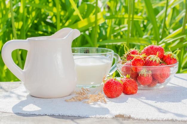 Un bol de fraises, une tasse de lait et un pichet sur une serviette de table sur une table en bois Photo Premium