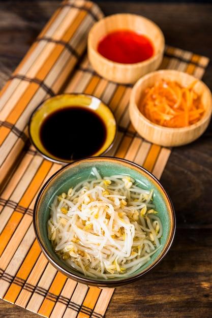 Bol de haricots germés avec sauce soja et piment rouge sur napperon Photo gratuit