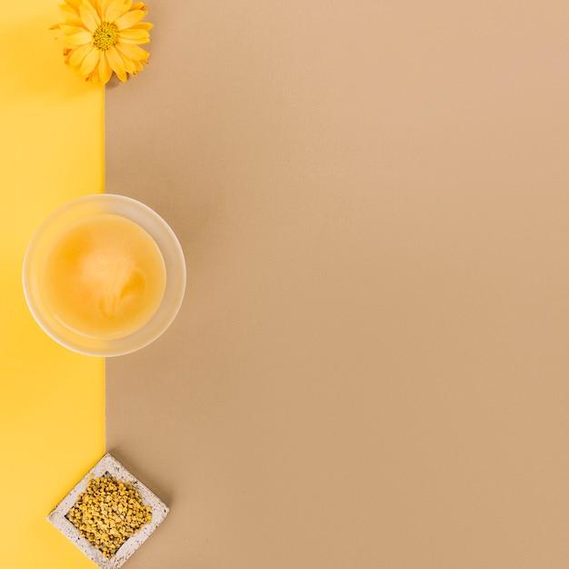 Bol de lait caillé au citron; graines de pollen d'abeille et fleur sur fond bicolore Photo gratuit