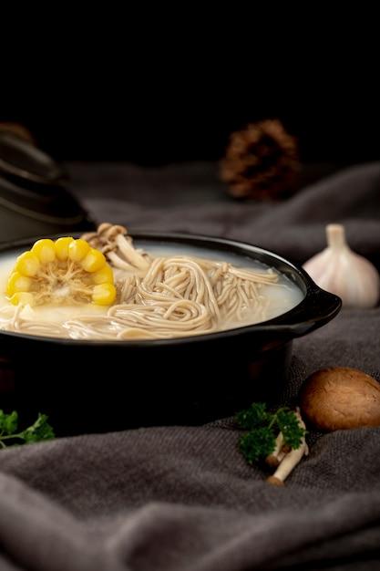 Bol noir rempli de soupe de nouilles et de maïs sur un drap gris à l'ail et aux champignons Photo gratuit