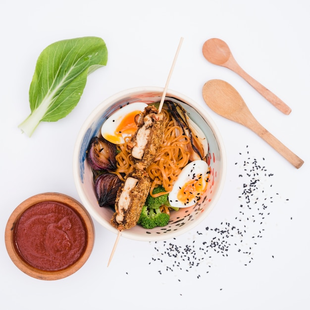Bol de nouilles aux légumes et oeufs à la sauce; graines de sésame et cuillère en bois sur fond blanc Photo gratuit