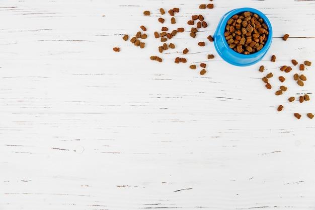 Bol de nourriture pour animaux de compagnie sur une surface en bois blanche Photo gratuit