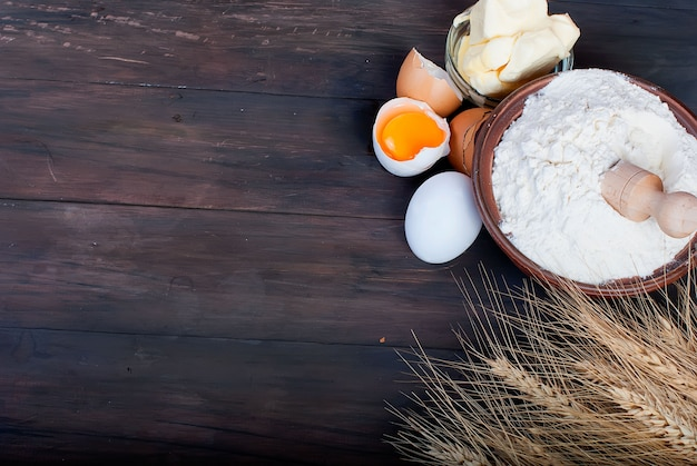 Bol avec des œufs de farine épis de blé et de beurre sur le concept de nourriture et de boissons vintage planche de bois Photo Premium