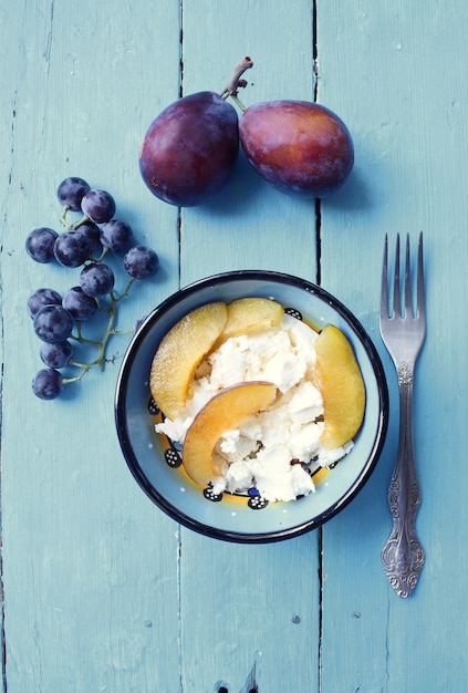 Bol petit-déjeuner sain avec des prunes, des raisins et du fromage à la crème. Photo gratuit
