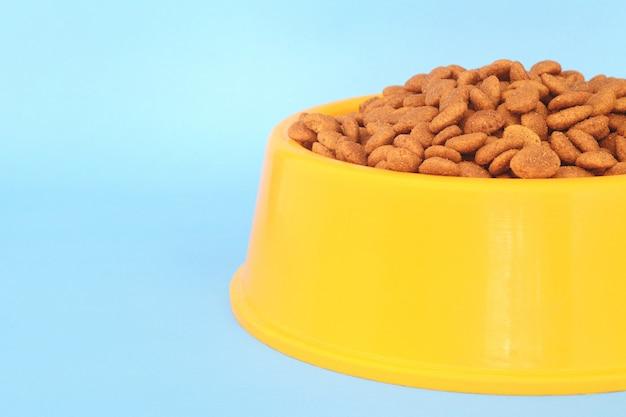 Bol en plastique jaune rempli de nourriture pour chien Photo Premium