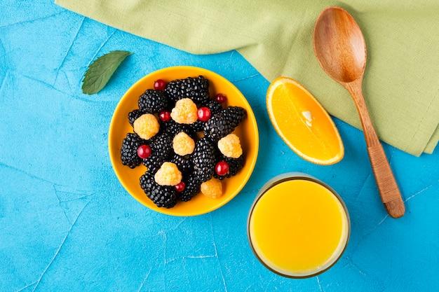 Bol à plat de baies fraîches et de fruits avec du jus Photo gratuit