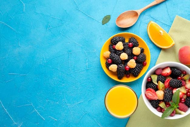 Bol à plat de baies fraîches et de fruits avec fond Photo gratuit