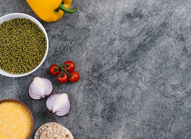 Bol de polenta et haricots mungo; oignon; tomates cerises; gâteau aux oignons et riz soufflé sur fond de béton gris Photo gratuit