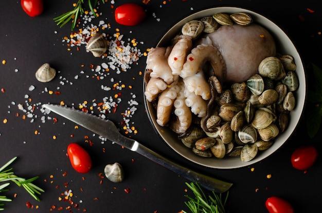 Un bol avec des poulpes frais aux palourdes et des ingrédients pour cuisiner sur un fond noir Photo Premium