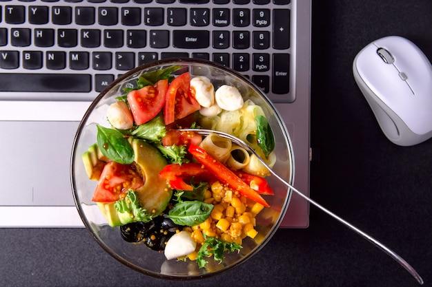 Bol de salade de légumes avec mozzarella, laitue, tomate, poivron et concombre sur le bureau à côté de la souris Photo Premium