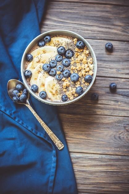 Bol de smoothie aux baies pour petit-déjeuner équilibré avec banane, granola, bleuets et graines de chia Photo Premium