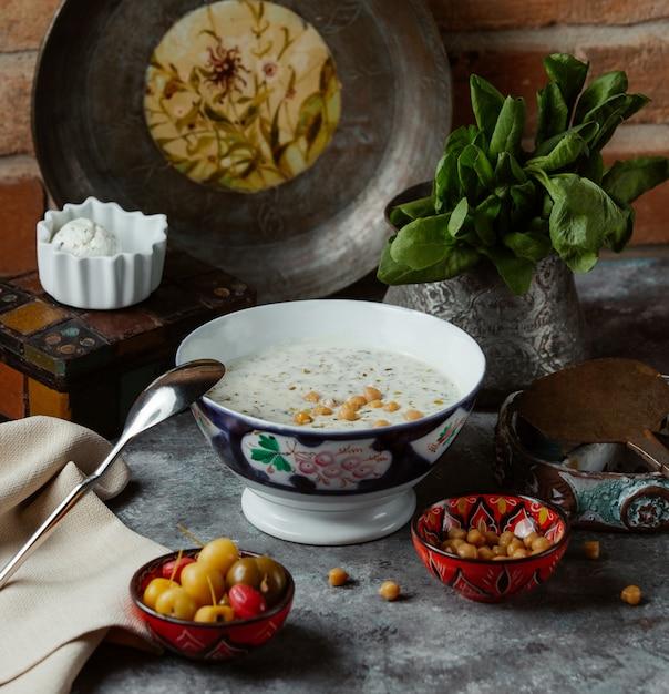 Un bol de soupe au yogourt traditionnel avec des haricots jaunes à l'intérieur, servi avec des légumes marinés Photo gratuit