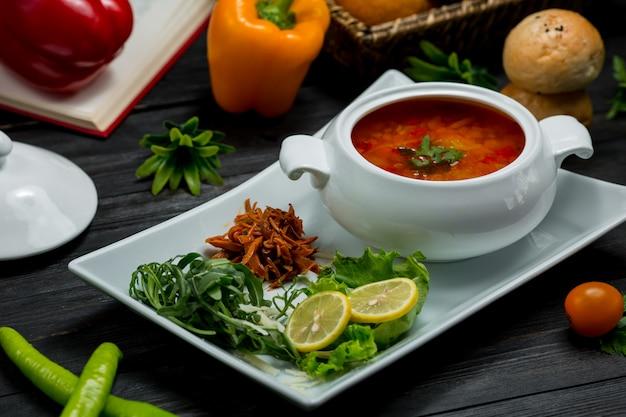 Un bol de soupe aux légumes dans un bouillon servi avec une salade verte au citron Photo gratuit