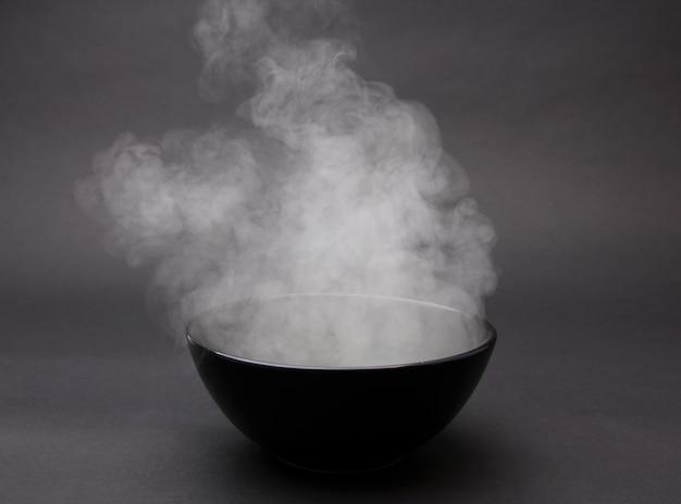 Bol de soupe chaude sur fond noir Photo Premium