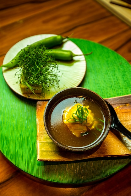Un bol de soupe japonaise et une assiette de poivrons verts et d'herbes Photo gratuit