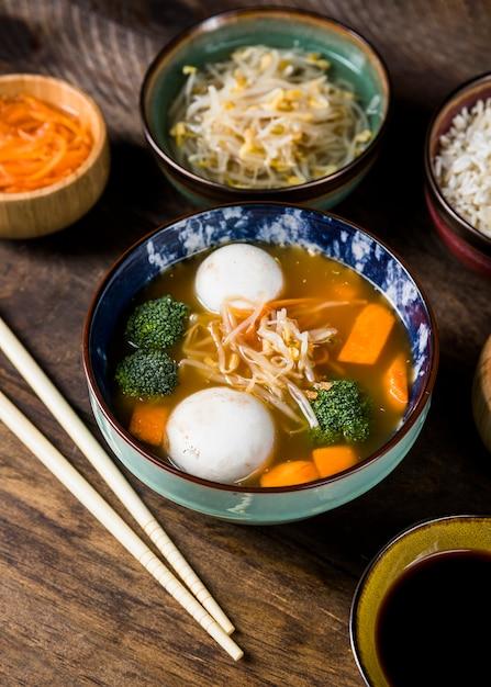 Bol de soupe de poisson et de poisson, servi avec pousses de haricots et carotte râpée sur une table en bois Photo gratuit