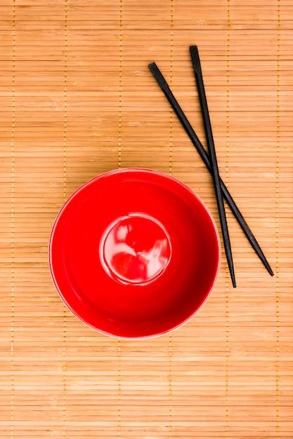 Bol de style asiatique rouge avec des baguettes sur un napperon texturé Photo gratuit
