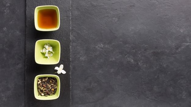 Bol de thé et son ingrédient disposer en rangées sur une pierre d'ardoise sur une surface noire Photo gratuit