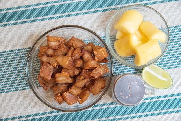 Bol transparent avec crépitant de manioc, citron et sel sur fond rayé Photo Premium