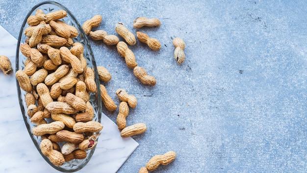 Bol en verre de cacahuètes entières avec des coquilles sur fond de granit Photo gratuit
