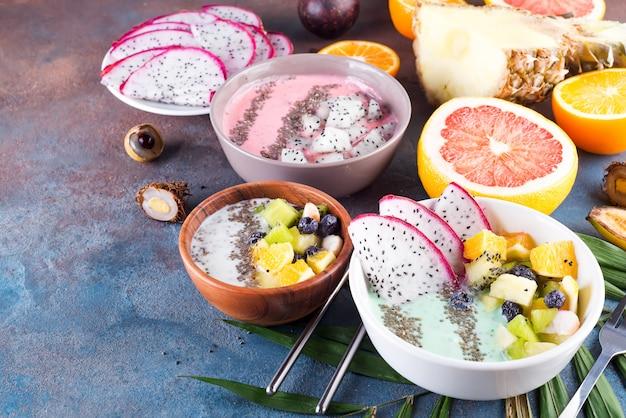 Bol de yaourt vert de petit déjeuner garni de pitaya, ananas, graines de chia et baies à la feuille de palmier sur fond de pierre, vue de dessus Photo Premium