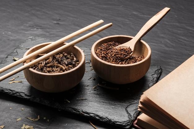Bols en bois avec insectes sur ardoise Photo gratuit