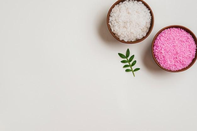 Bols de sel rose et blanc avec des feuilles vertes sur fond blanc Photo gratuit