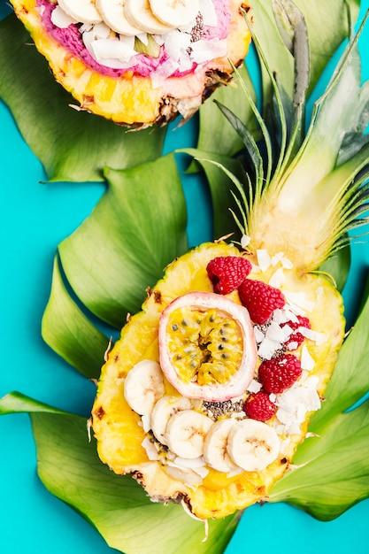 Bols à smoothies servis à l'ananas coupé sur bleu Photo Premium