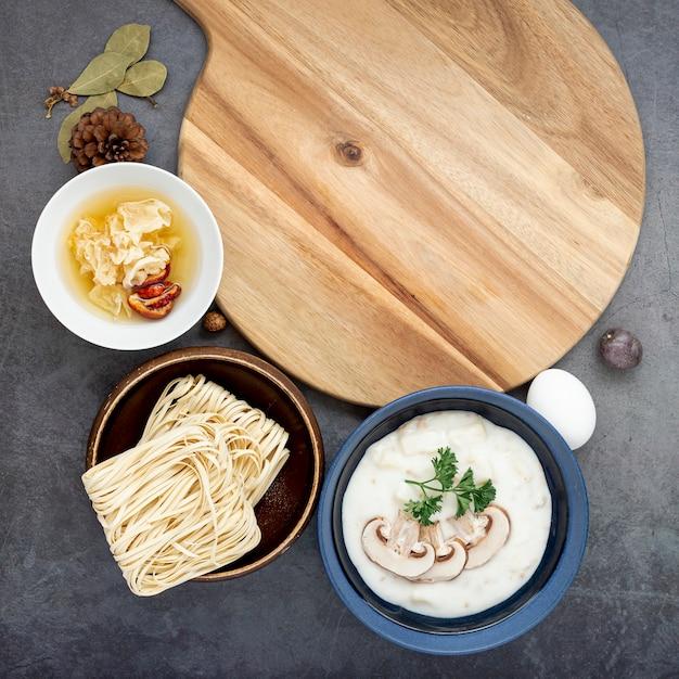 Bols à soupe de nouilles et de champignons sur fond gris avec un support en bois Photo gratuit