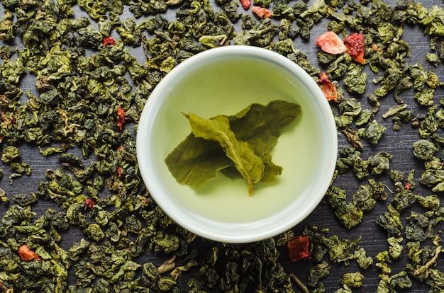 Bols avec thé oolong vert feuille et fraises Photo Premium