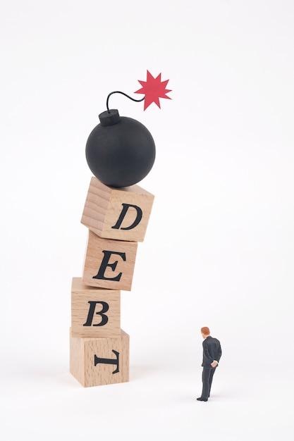 Bombe sur le mot dette écrit en cubes en bois Photo Premium