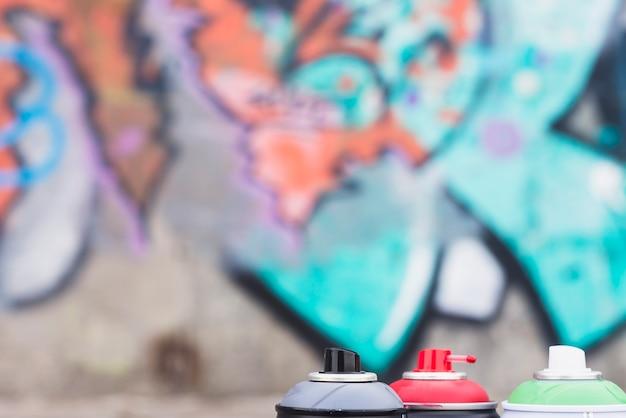 Des bombes aérosol devant un mur de graffitis Photo gratuit