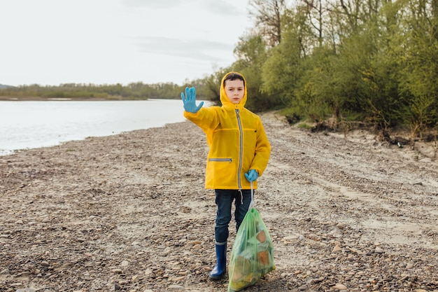Le bon garçon bénévole jettera les sacs à ordures noirs à la poubelle. le garçon a des ordures malodorantes. Photo Premium