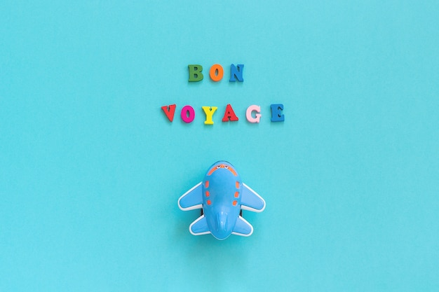 Bon voyage texte coloré et avion jouet drôle sur papier bleu Photo Premium