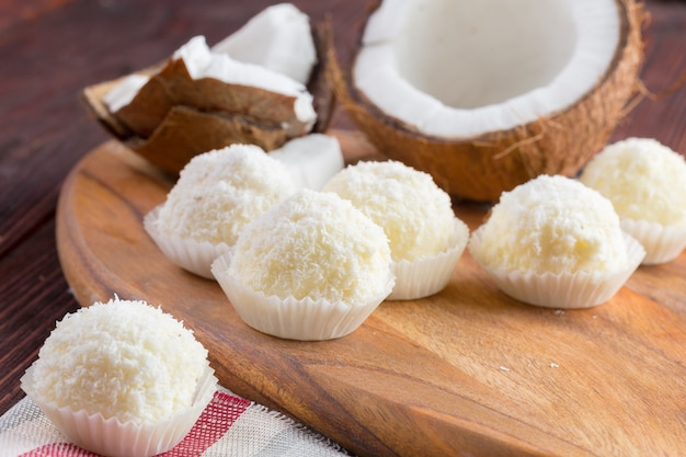 Bonbons Au Chocolat Blanc Avec Garniture De Noix De Coco Sur Table En Bois Photo Premium