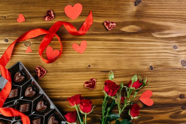 Bonbons au chocolat avec des roses sur la table Photo gratuit
