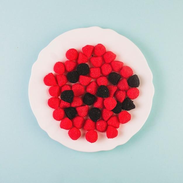 Bonbons aux canneberges rouges et noirs sur une assiette Photo gratuit