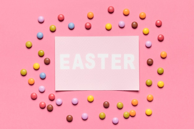 Bonbons aux pierres colorées entourés autour du papier avec le mot de pâques sur fond rose Photo gratuit