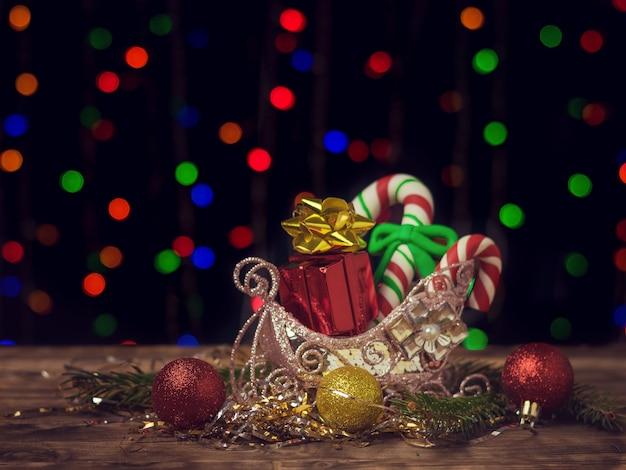 Bonbons Et Cadeaux De Noël Dans Un Panier Décoratif Sur Une Table En Bois Photo Premium
