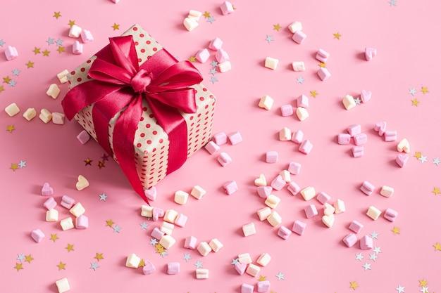 Bonbons Et Coffret Cadeau Avec Noeud Rouge Sur Surface Rose. Photo gratuit