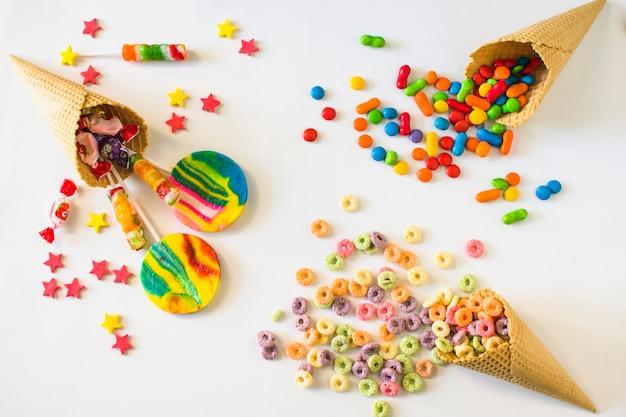 Bonbons colorés avec cornet de crème glacée à la gaufre sur fond blanc Photo gratuit