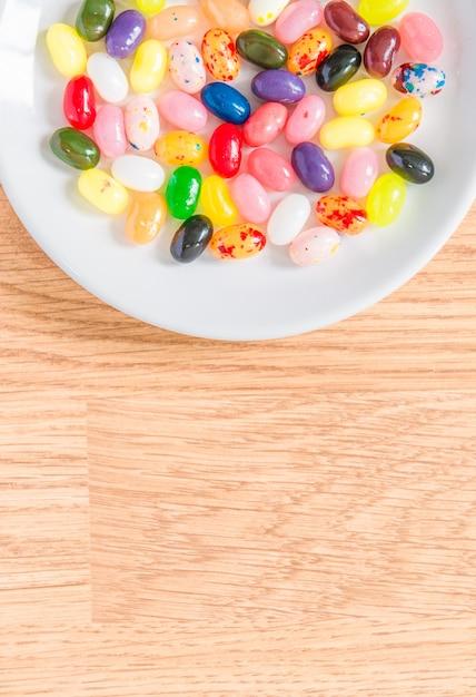 Bonbons colorés dans une assiette blanche Photo Premium