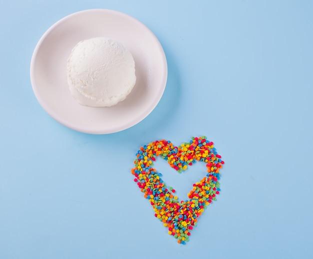 Bonbons colorés en forme de coeur et de crème glacée sur le fond bleu. Photo Premium