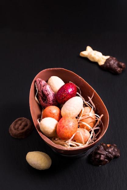 Bonbons colorés et œufs de pâques au chocolat sur une plaque d'ardoise noire avec espace de copie Photo Premium