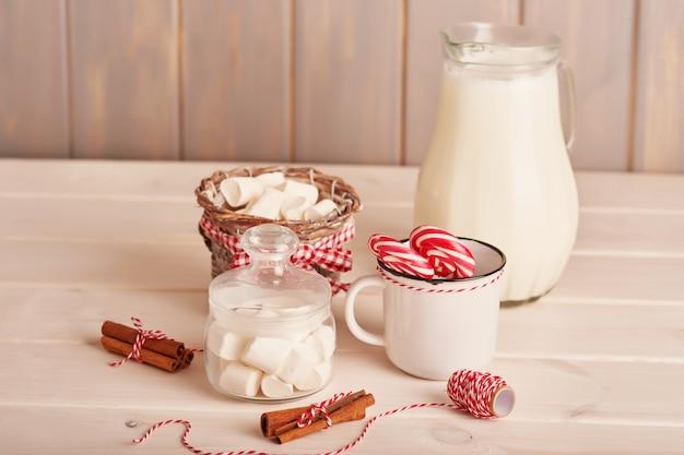 Bonbons du nouvel an guimauves, sucettes et lait sur la table avec des cadeaux Photo Premium