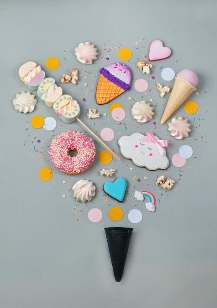 Bonbons en forme de crème glacée avec cône de gaufre noir sur fond gris Photo Premium
