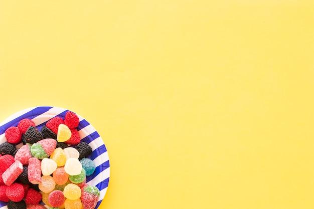 Bonbons à la gelée sur une plaque à rayures sur le fond jaune Photo gratuit