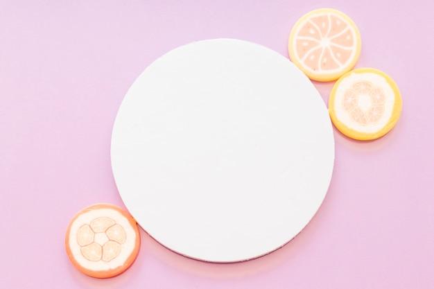 Bonbons gelée de sucre près du cadre circulaire blanc blanc sur fond rose Photo gratuit
