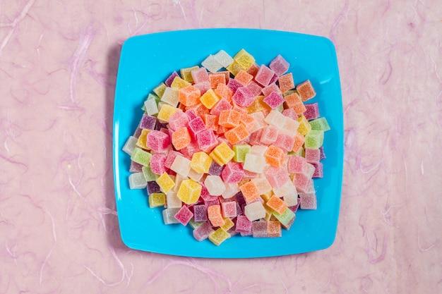 Bonbons Et Gelées En Plat De Couleur Sur Fond Rose Photo Premium