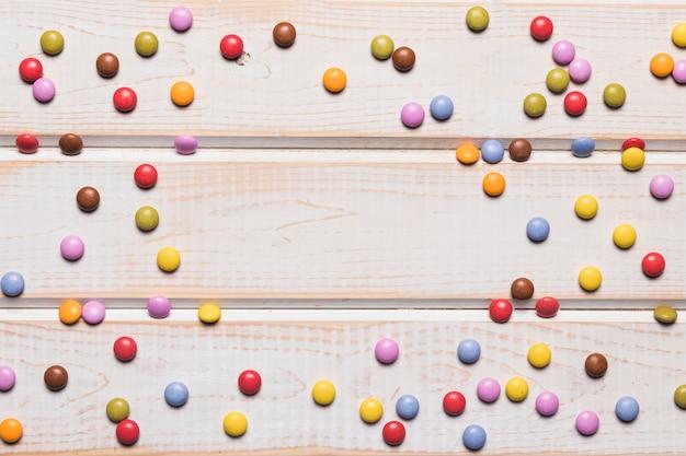 Bonbons gem répartis sur le bureau en bois avec un espace au centre Photo gratuit